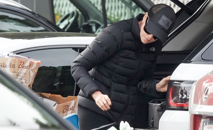 Charlize Theron wears a black stretch down jacket from The North Face