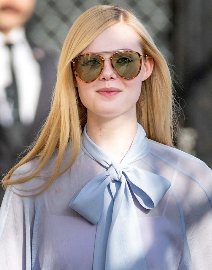 Elle Fanning wears her blonde hair straight with a side parting