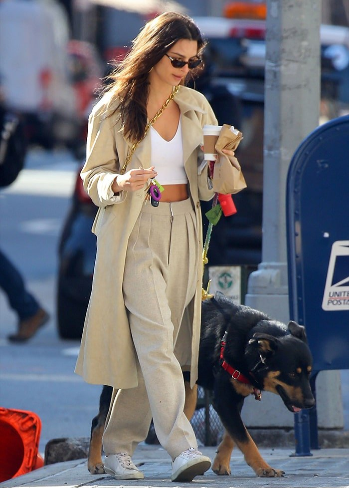 Emily Ratajkowski wears a white crop top with cream coat and trousers