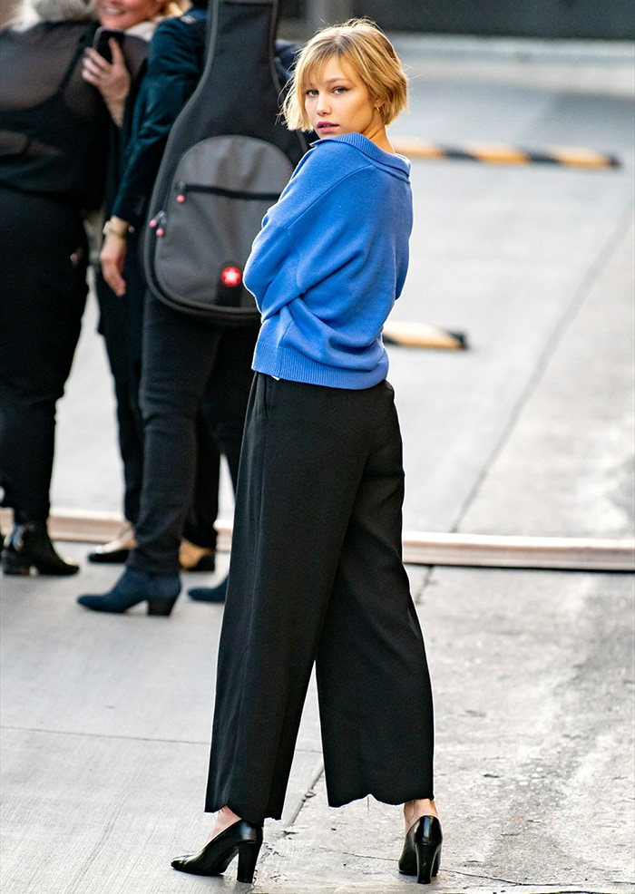 Grace VanderWaal in a blue sweater and loose-fitting black trousers outside the studio