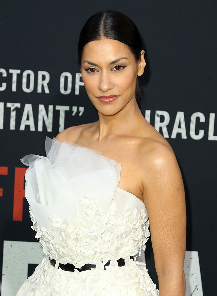 Janina Gavankar wears her dark tresses in a center-parted bun with cat eye-makeup and rosy lip shade