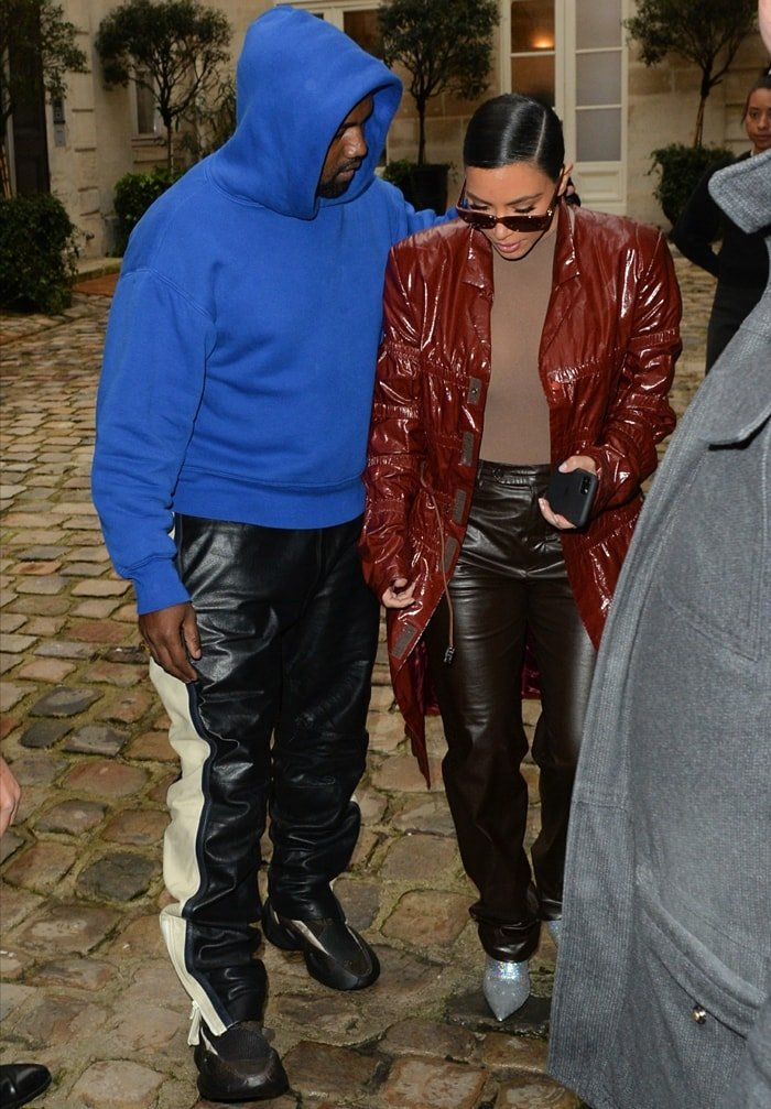 Wearing a brick red trench coat, Kim Kardashian West is seen with her husband Kanye West