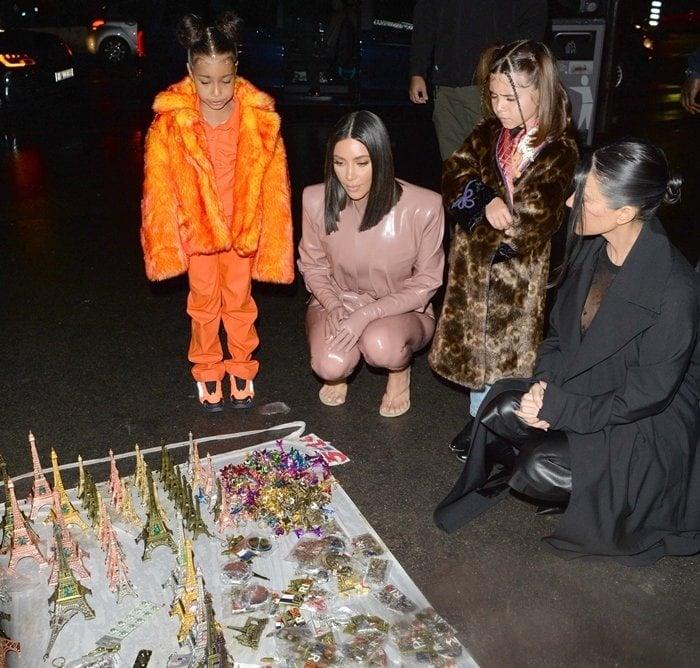 Kim Kardashian, North West, Penelope Disick, and Kourtney Kardashian are seen near the Eiffel Tower