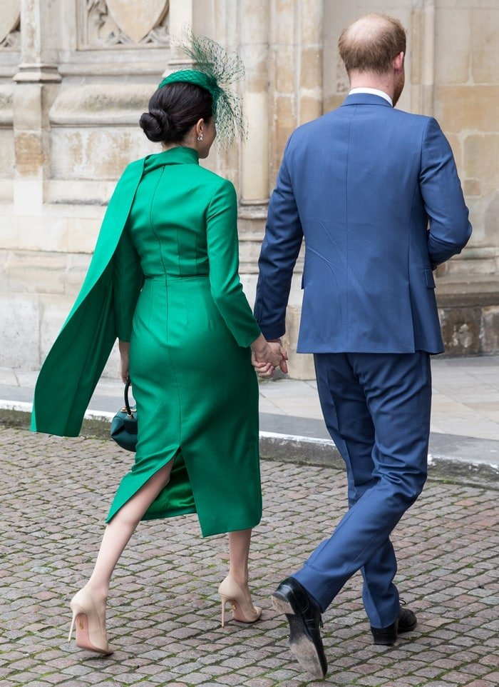 Meghan Markle wore a green pleated midi dress featuring a band collar, a button fastening, a fitted waist, long sleeves, a straight hem, and a back zip fastening