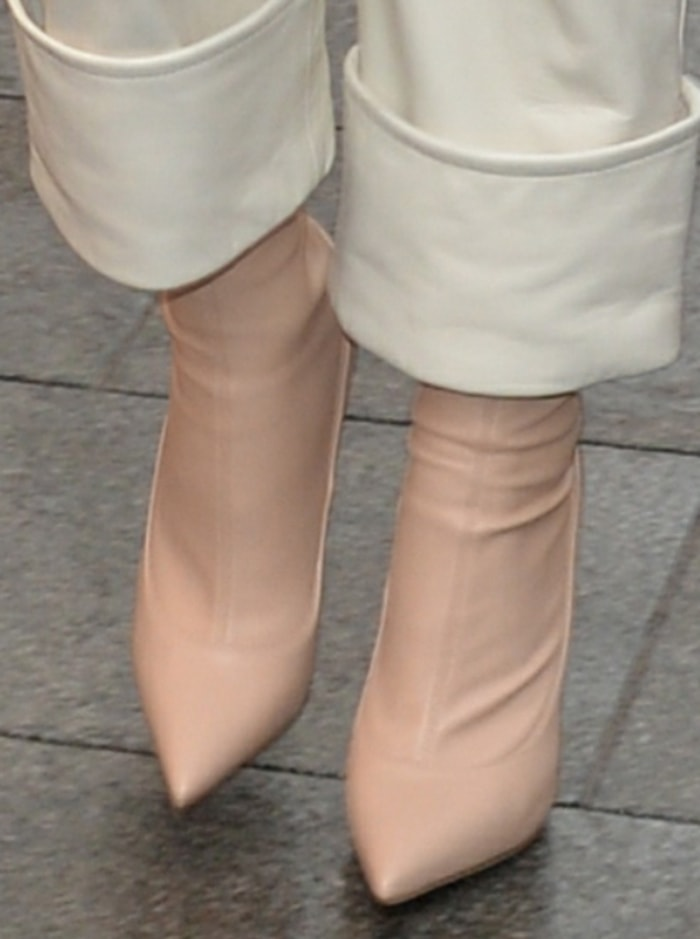 Rita Ora slips into a pair of pink skintight boots