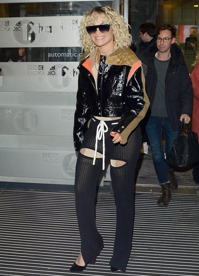 Rita Ora in skintight jumpsuit worn underneath a leather jacket and rib-knit trousers