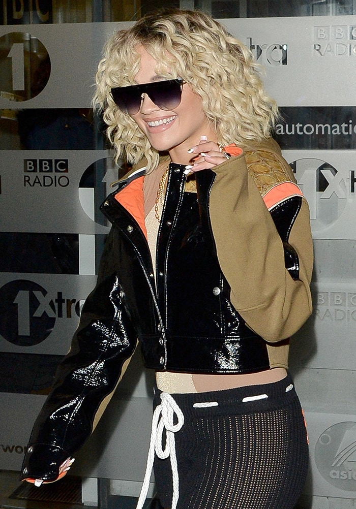Rita Ora styles her blonde tresses in voluminous curls and wears nude lipstick