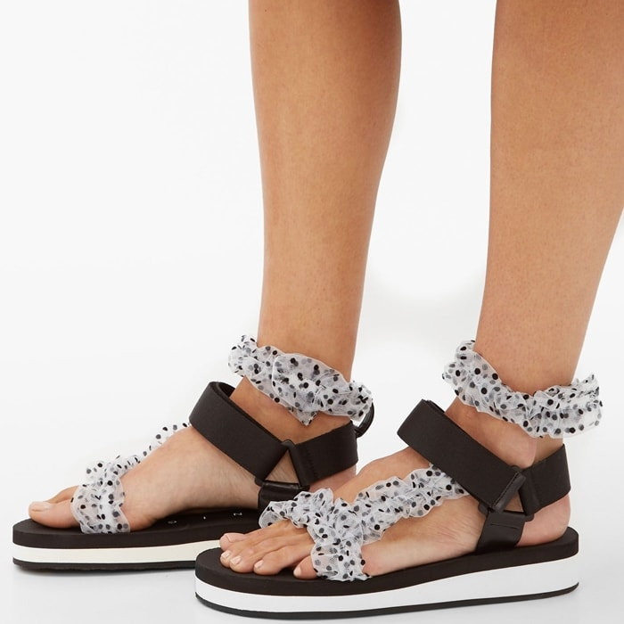 The black and white design offers polka-dotted straps around the toe and ankle with a velcro fastening