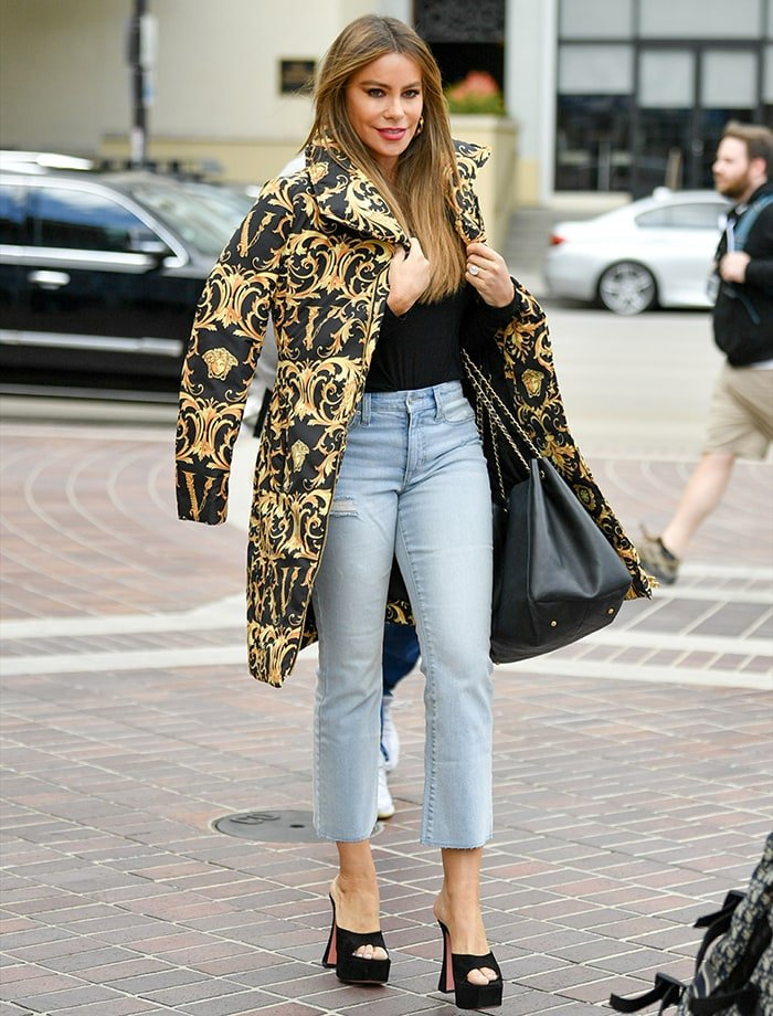 Sofia Vergara wears a Versace baroque puffer coat over a black sweater and faded jeans