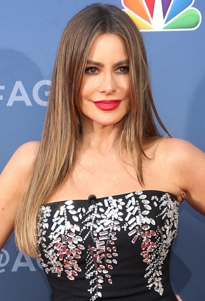 Sofia Vergara shows a fierce look with red lipstick, smokey eyes, and her hair straight and down