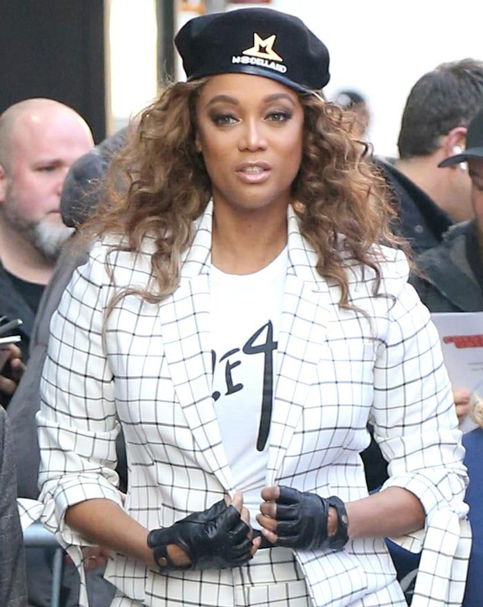 Tyra Banks wears voluminous curls underneath her ModelLand beret hat