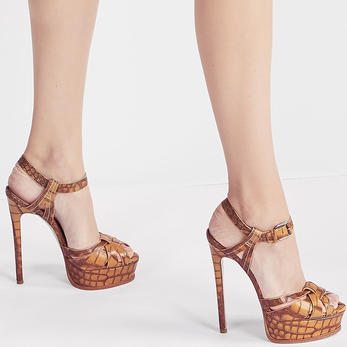 The iconic Casadei platforms with their vertiginous heels made to highlight the feminine silhouette are offered in an antique well worn crocodile print that gives them an elegant everyday look