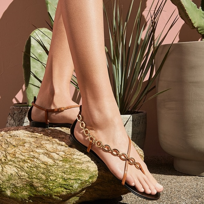 These flat leather sandals are embellished by a chain connecting the leather straps