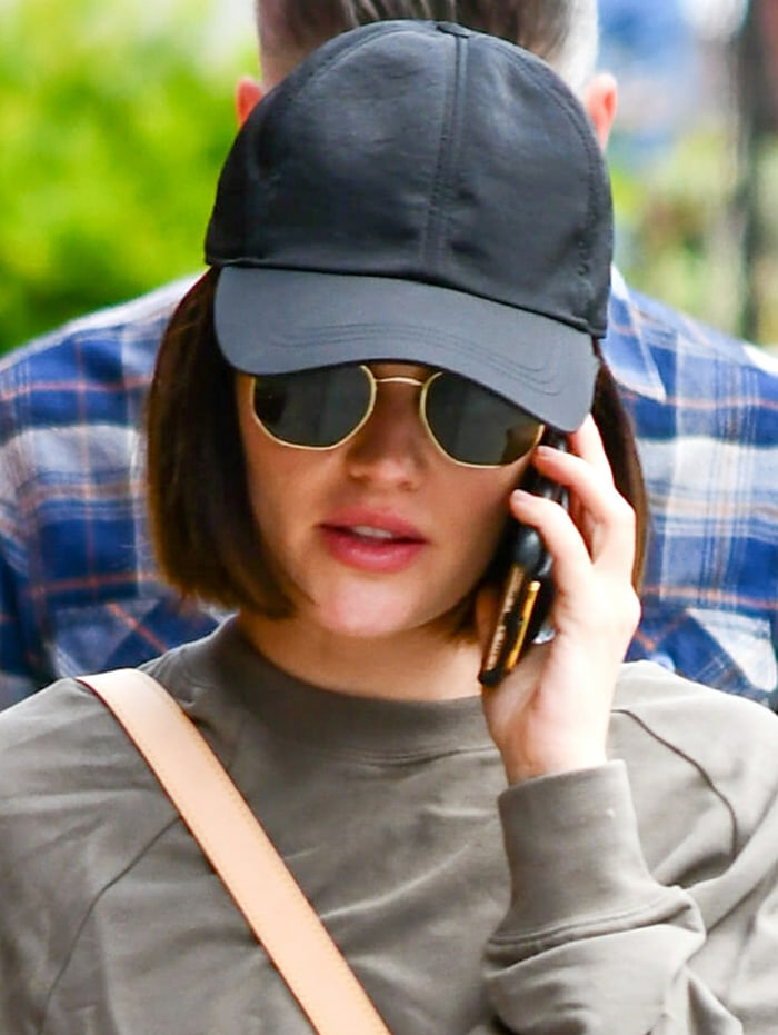 Lucy Hale keeps things low-key with sunglasses and a black cap