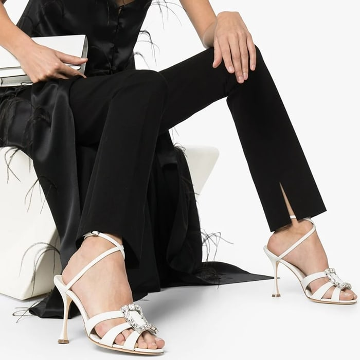 Step away from toxic people and step into these white Ticuna 105mm crystal sandals from Manolo Blahnik that have a striking central buckle that shimmers with every step you take and instantly peps you up with its high stiletto heel