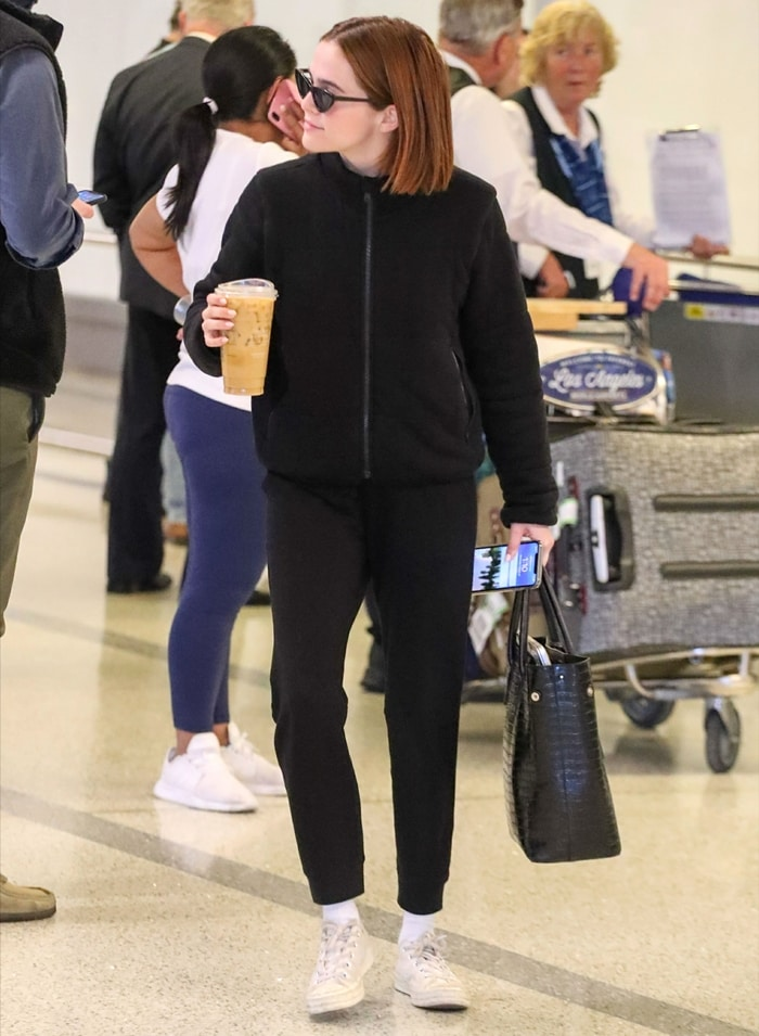 Zoey Deutch at Los Angeles International Airport wearing a black outfit with comfortable travel sneakers