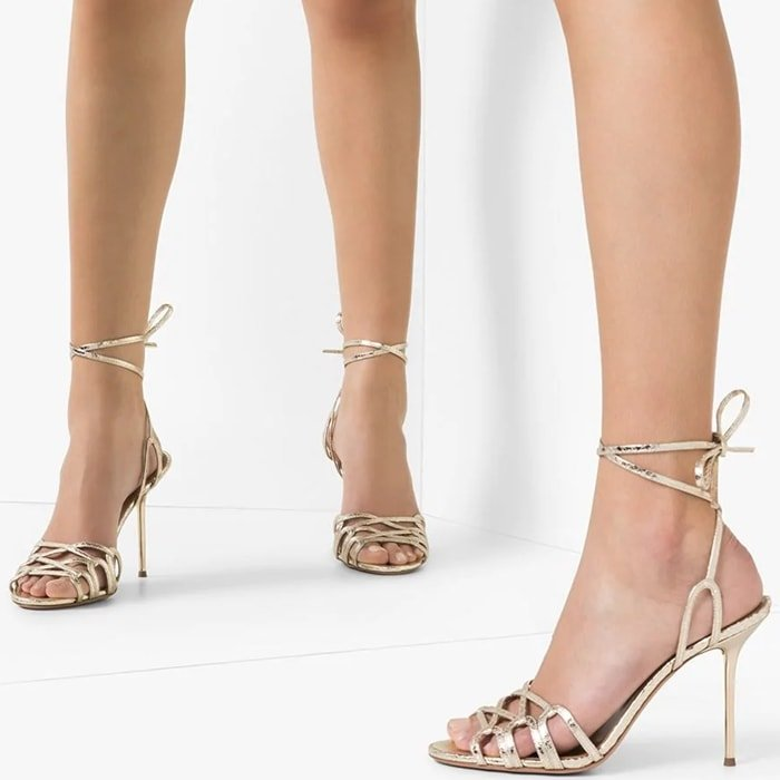 Delicate snakeskin-embossed metallic leather straps encircle the ankle and cross the toes of these stiletto sandals