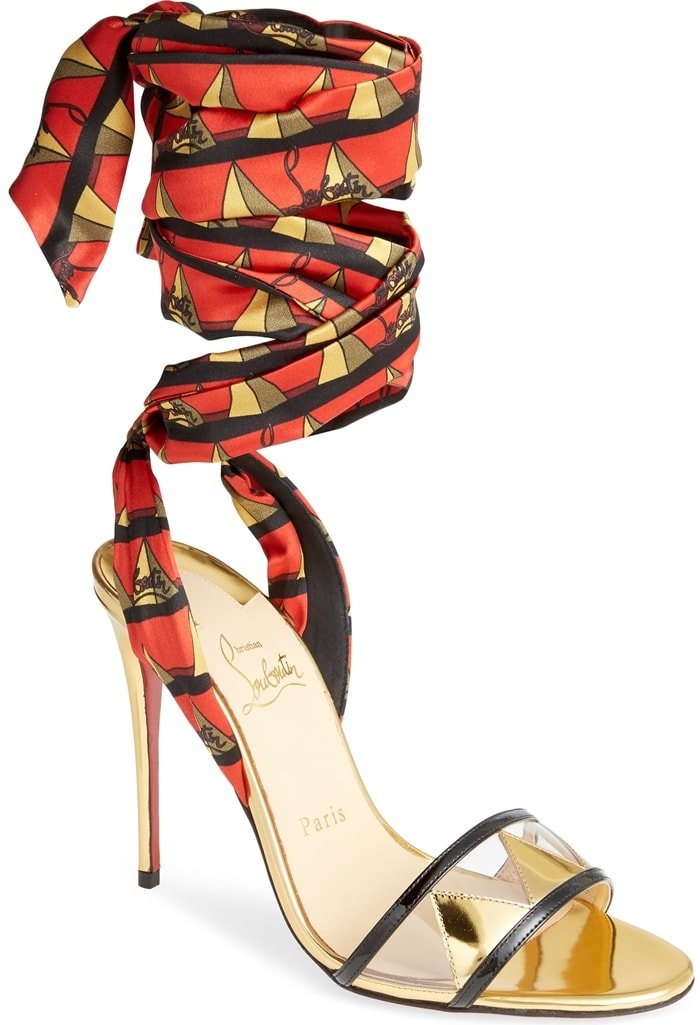 Golden triangles on the clear strap pick up the geometric print on the ankle wraps of a jaunty metallic sandal set on a slender stiletto heel