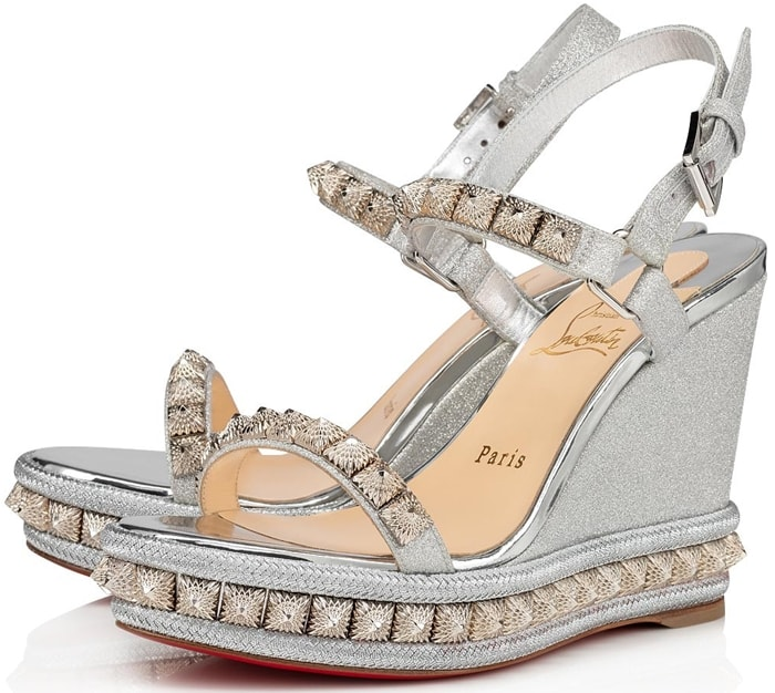 Set atop a platform wedge sole, these glittering sandals are elevated with faceted metallic studs