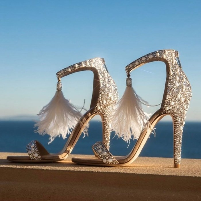 An ostrich-feather tassel adds an ethereal touch to the ankle strap of a stiletto-lifted sandal with sparkling crystals adding to the glamorous look