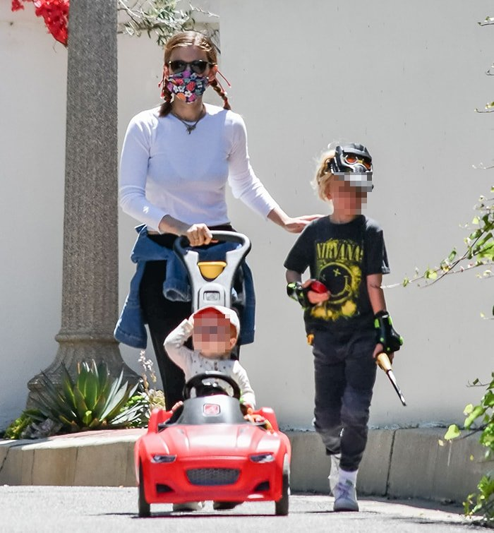 Kate Mara wraps her jacket around her waist as she pushes her daughter in a red car-shaped buggy