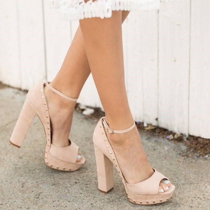 An open-toe blush pump with a chunky platform, stud detailing, and side buckle closure