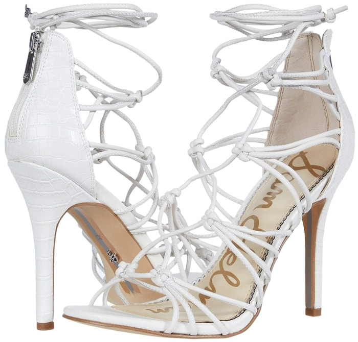 Slim straps are knotted together and woven up the vamp of a summery white sandal lofted by a tapered heel