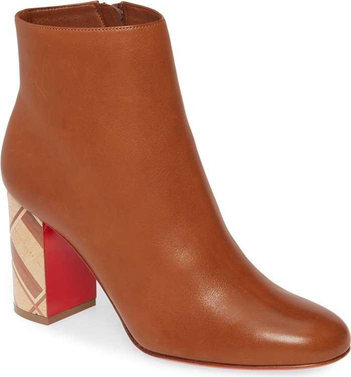 A beautifully carved block heel brings undeniable artistry to an Italian-crafted bootie in smooth, supple leather