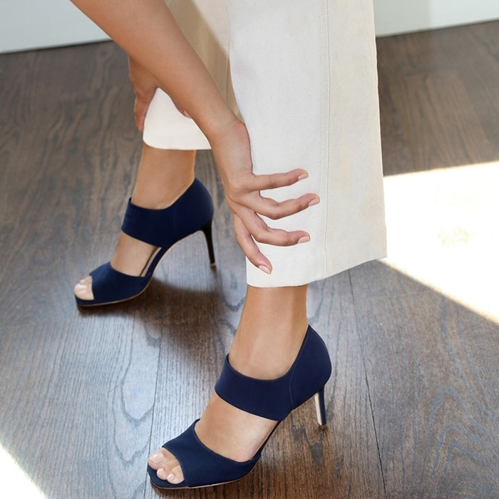 A tall, tapered heel lifts a sleek and stretchy square-toe sandal fitted with a cushioned footbed