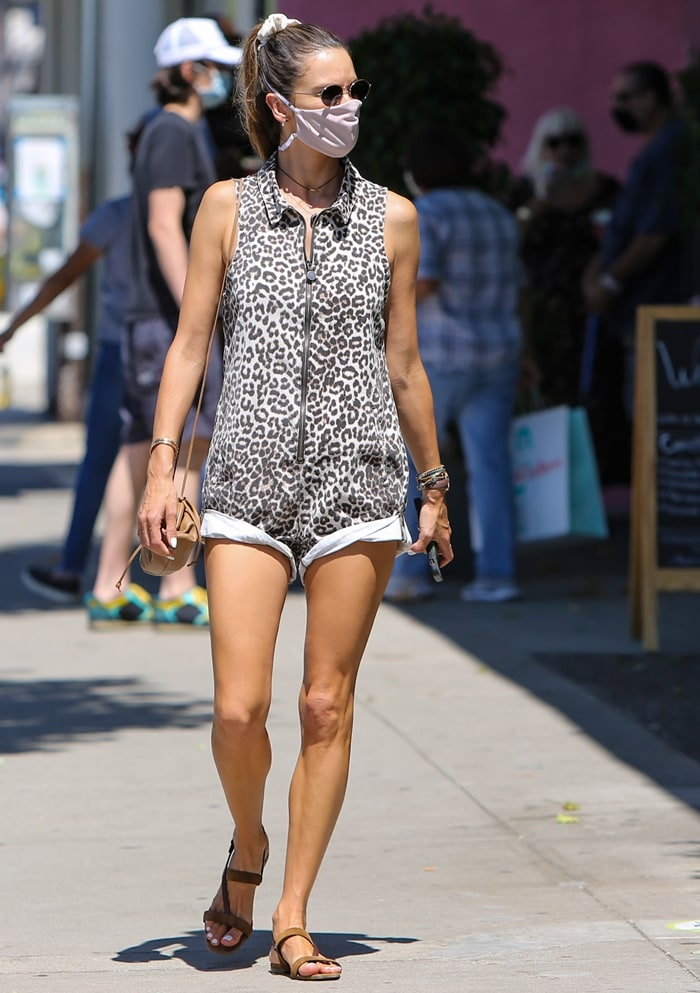 Alessandra Ambrosio's leopard print denim zip-up romper features a fitted body, drop waist, classic collar, vertical welt pockets, and back patch pockets