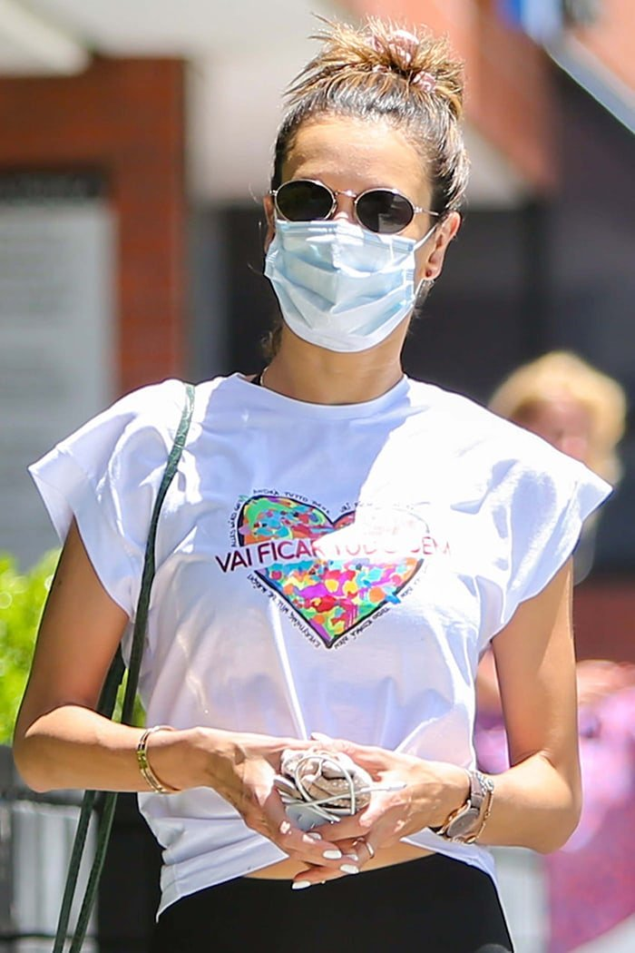 Alessandra Ambrosio keeps a low-key look with sunglasses, a facemask, and a top knot hairstyle