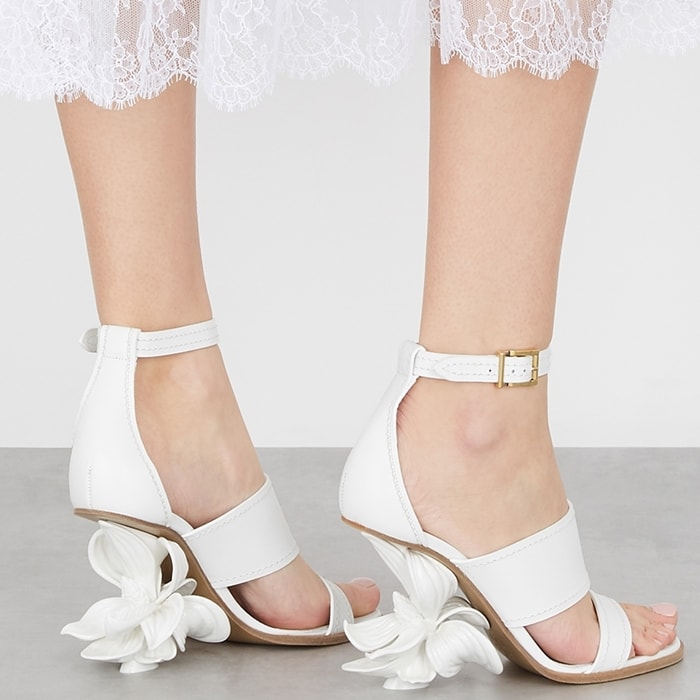 Decorated with a white bloom at the heel, these white wedge sandals have sturdy leather straps to keep your feet securely in place