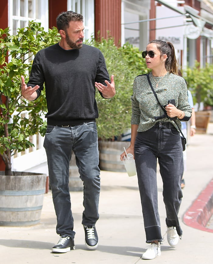 Ben Affleck wears a black sweater with black jeans and sneakers