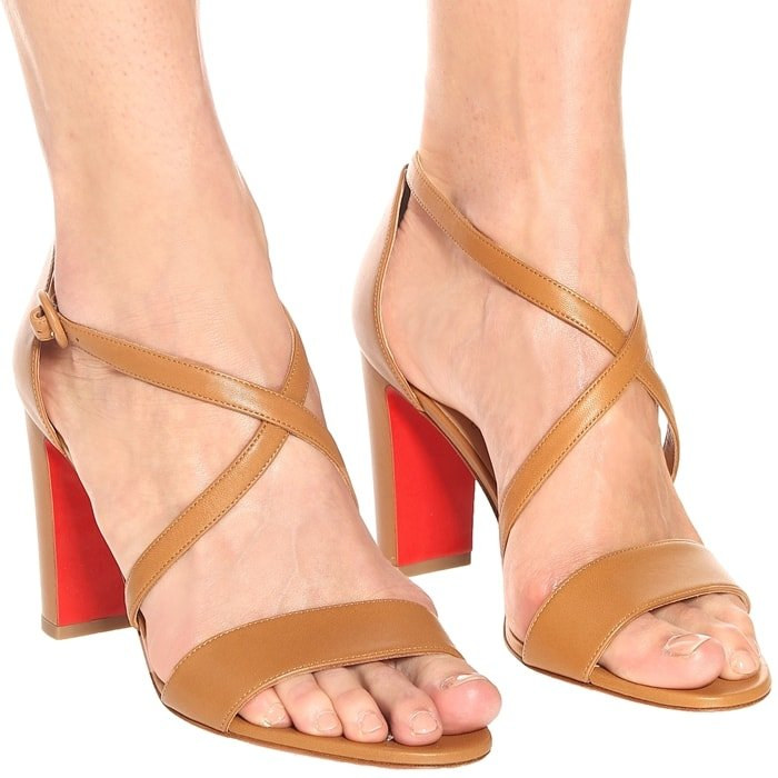 These brown Loubi Bee sandals from Christian Louboutin have slender straps that cross elegantly over the feet for sensual inflection