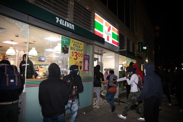 Demonstrators break into a 7-Eleven store during a protest over the death of George Floyd in New York
