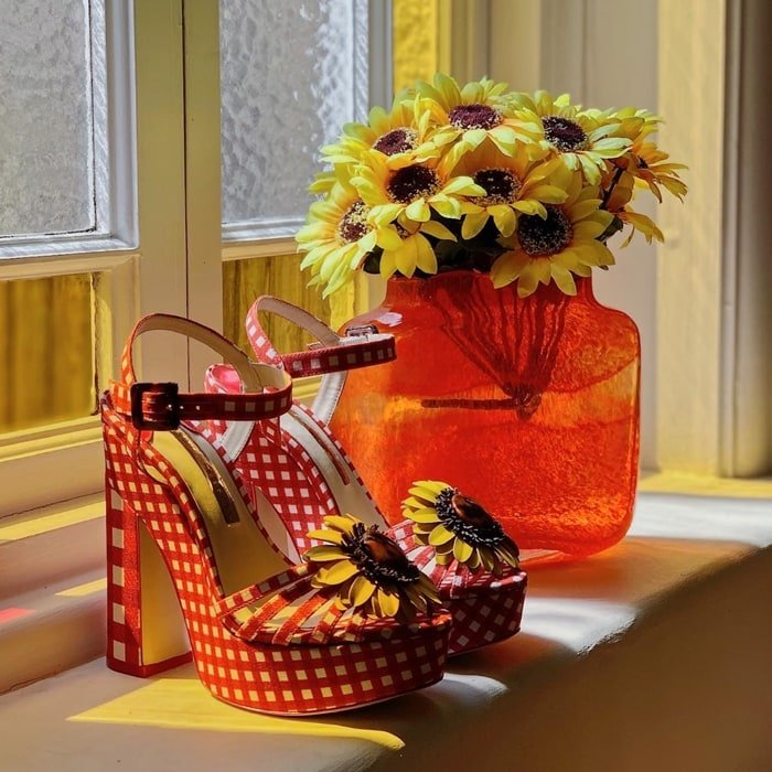 Sophia Webster favours whimsical, girlish ornamentation, demonstrated by the yellow leather floral embellishment that adorns these red gingham Doris sandals
