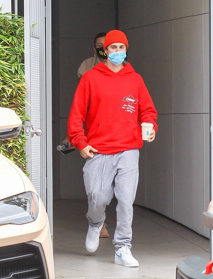 Justin Bieber in gray sweatpants with a red sweatshirt and matching beanie