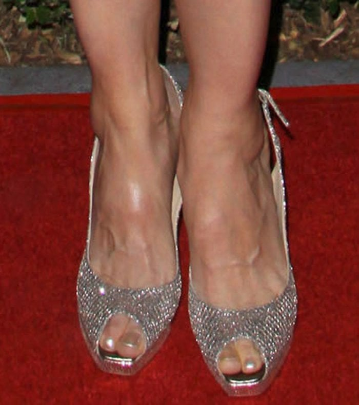 Lucy Lawless slips her big feet into a pair of metallic peep-toe slingback pumps