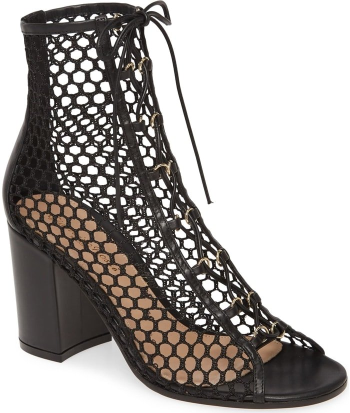 Inspired by fishnet stockings, a contour-hugging mesh sock makes a provocative statement on a lace-up bootie lifted by a bold block heel