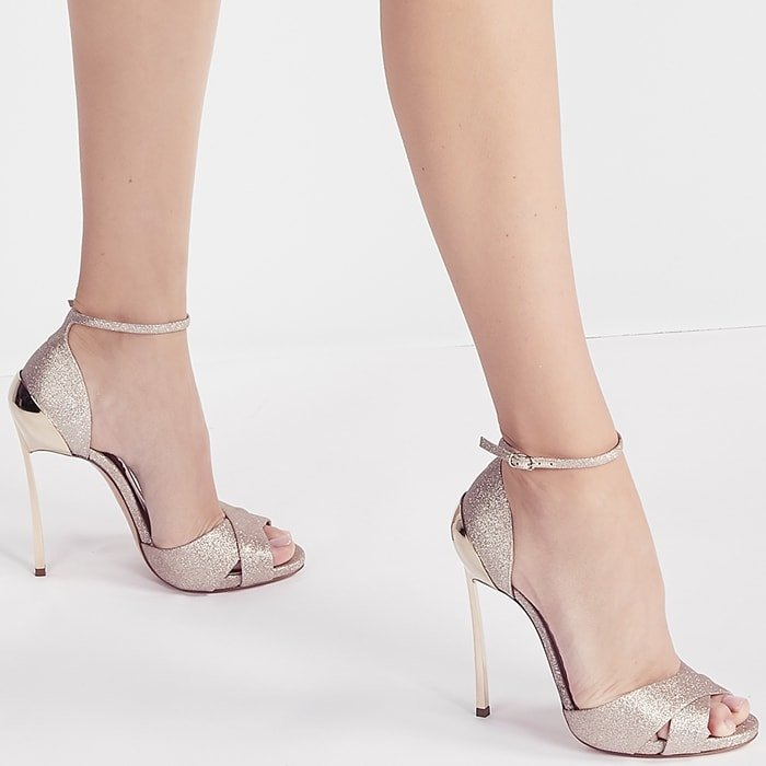 This model is the celebration of femininity thanks to the unique shape of the Techno Blade, composed of a golden mirrored shell that wraps around the heel of the foot and blends with the tone-on-tone heel, creating a unique chrome-plated structure