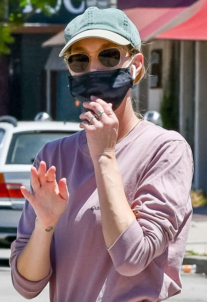 Whitney Port wears a black face mask for protection against coronavirus