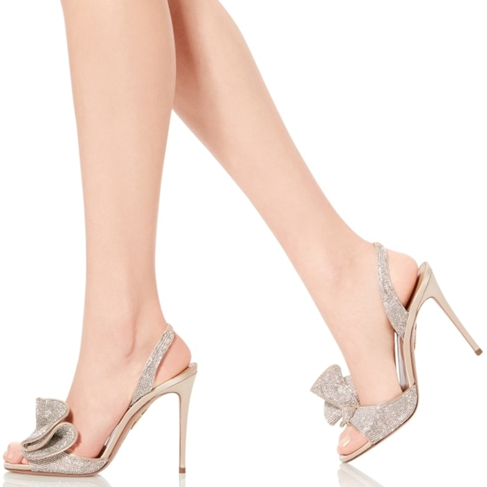 This sandal features a bow at the toe, a sleek ankle strap, and a pin-thin heel