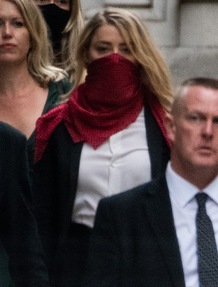 Amber Heard styles her black-and-white power suit with a red dotted scarf mask