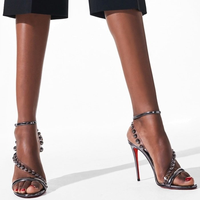 Silvery dome studs shine from clear straps on these metallic sandals set on a sky-high stiletto and finished with Louboutin's iconic red sole