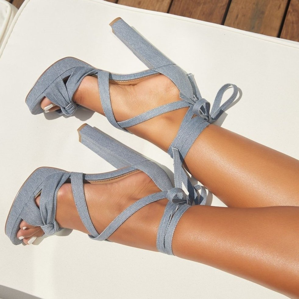 A blue denim strappy platform heeled sandal featuring a high block heel and wraparound ankle ties