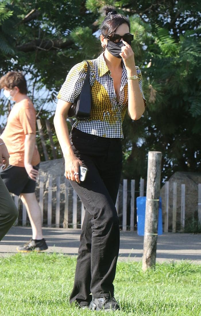 Dua Lipa wears a '90s Ottolinger gingham shirt with black slouchy pants