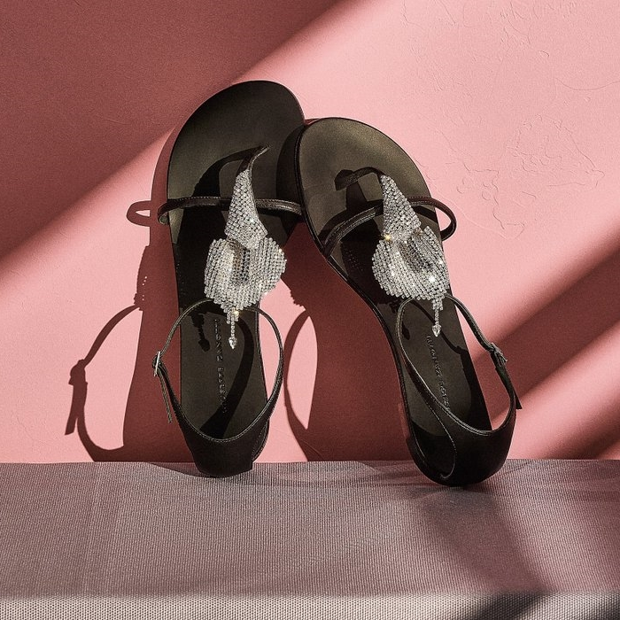 These flat, black leather strappy sandals are embellished by the 'Calla' crystal accessory