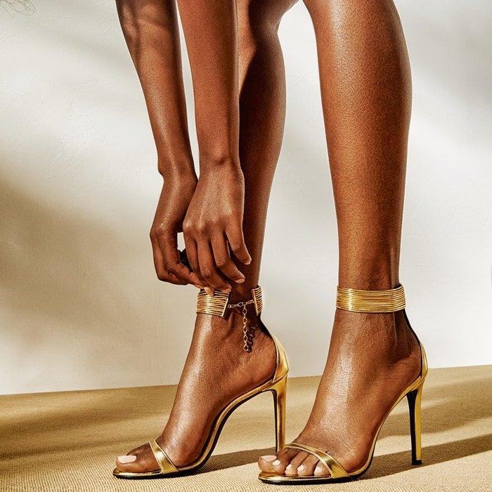 These high heel, laminated golden leather sandals feature a single front strap, and are characterized by their golden jewel anklet, doubling as an ankle strap