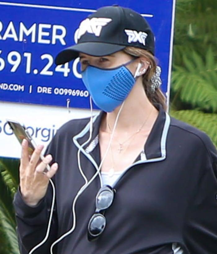 Katherine Schwarzenegger wears a blue face mask, a baseball cap, and a scrunchie