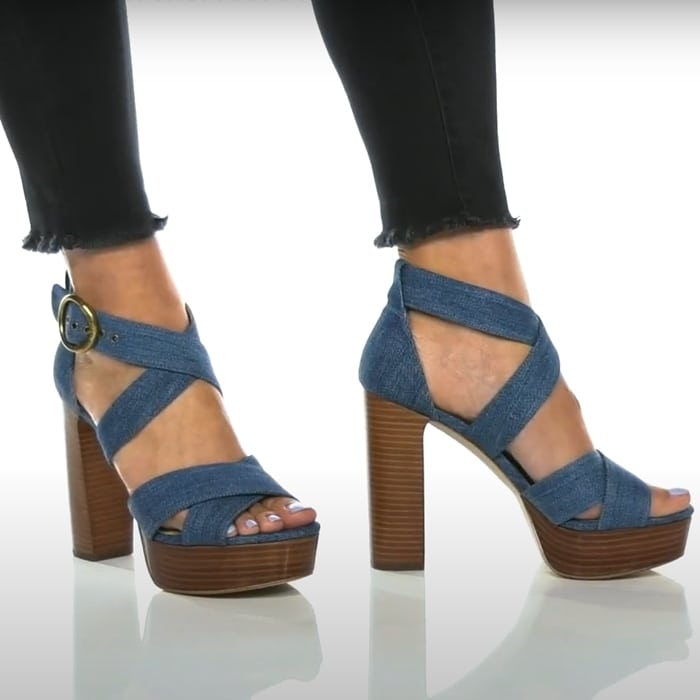 This light denim platform sandal is crafted with a leather upper, and features crisscross straps, and is set on a towering wooden heel